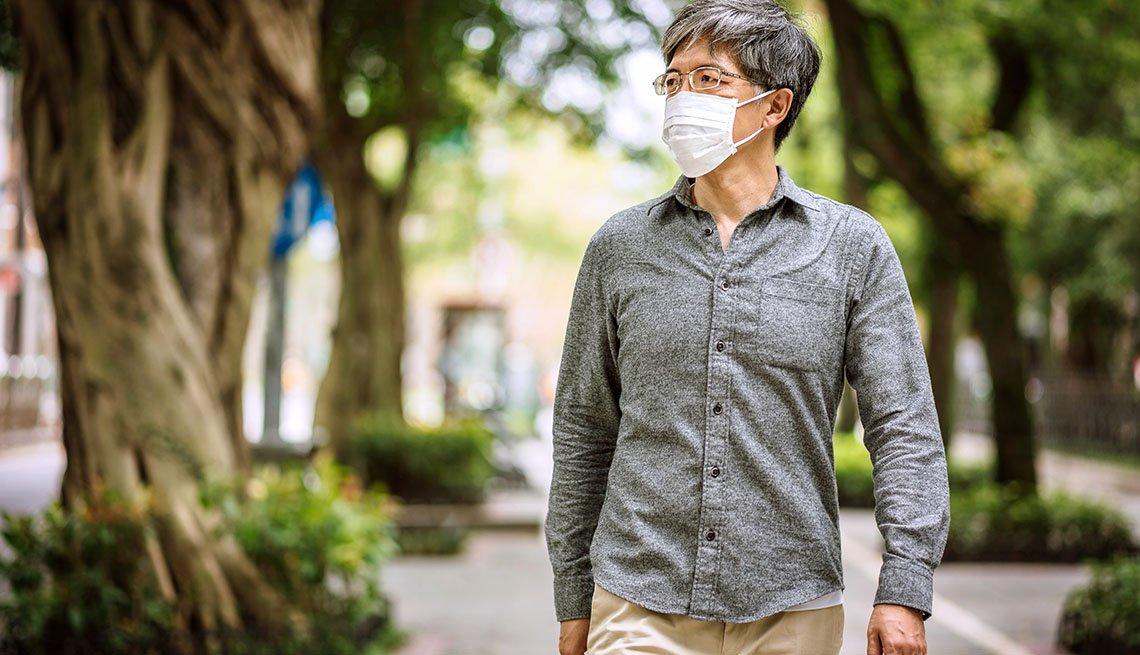 man in mask walking outside