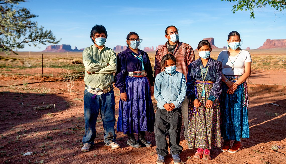 A Navajo family with the Monument Valley behind them stand together wearing masks for protection during the Coronavirus pandemic