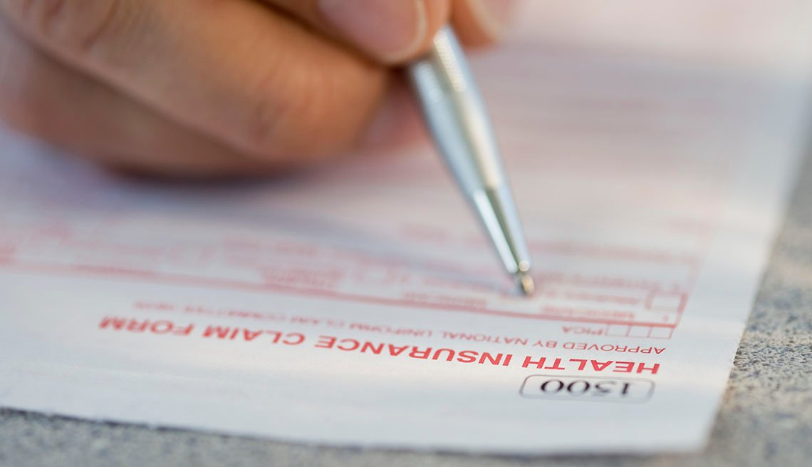 Persona llena un documento de una aseguradora médica
