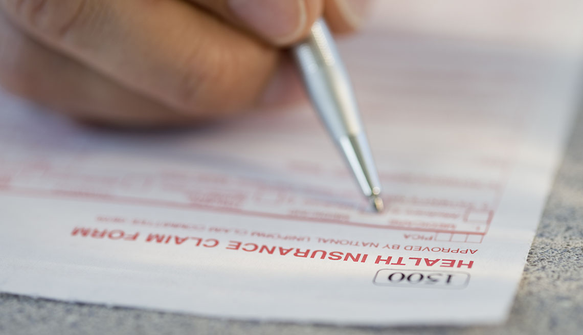 close up of person filling out a health insurance form
