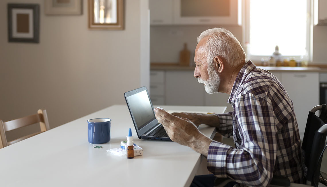 man in a wheelchair sits at a table and uses a computer