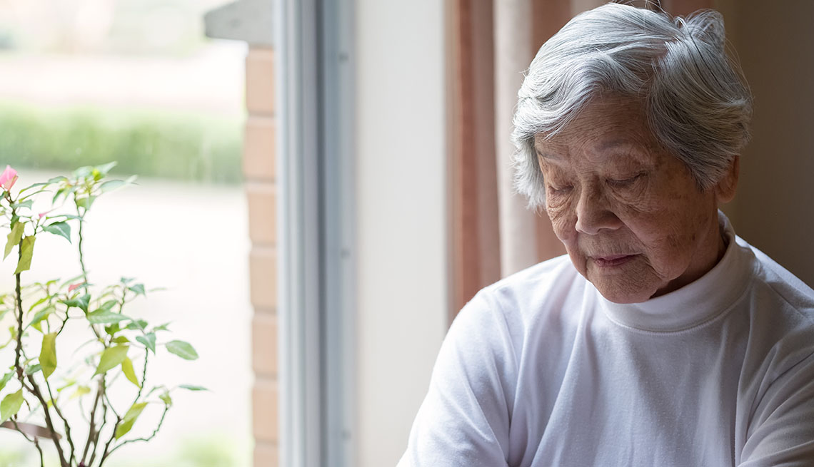 older woman sitting by window with eyes closed