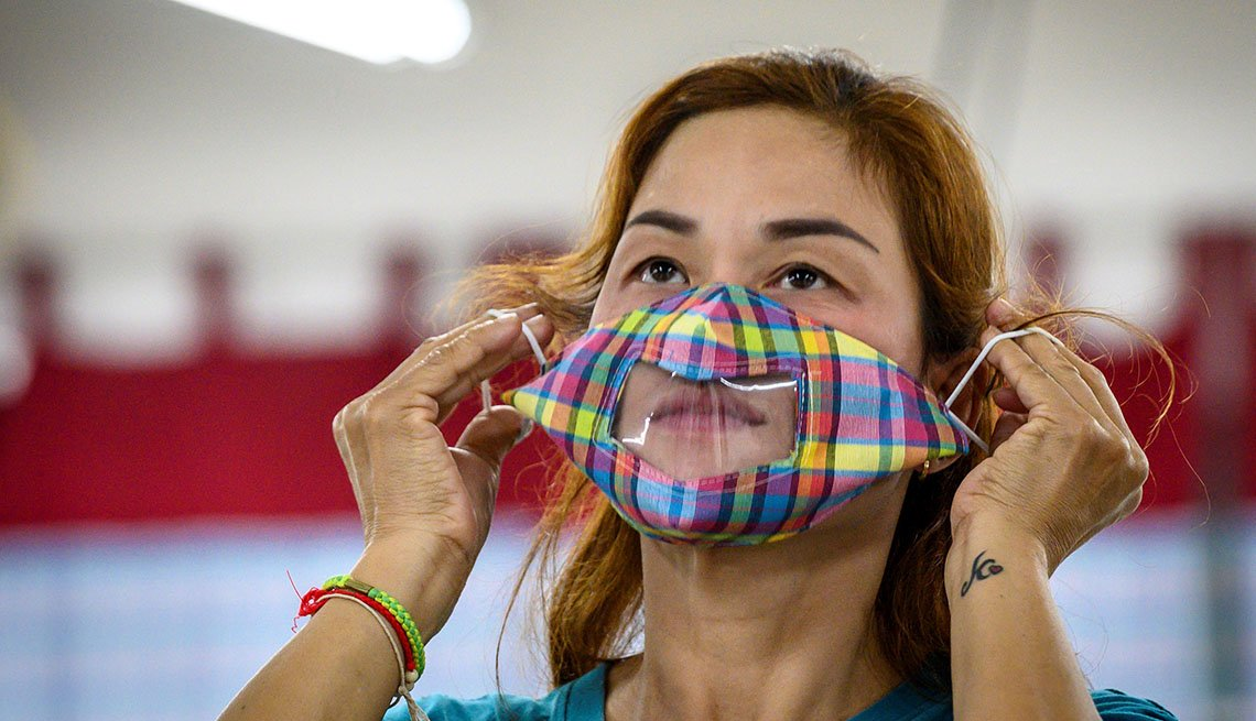 a woman uses a see-through face mask designed for deaf or hard of hearing people