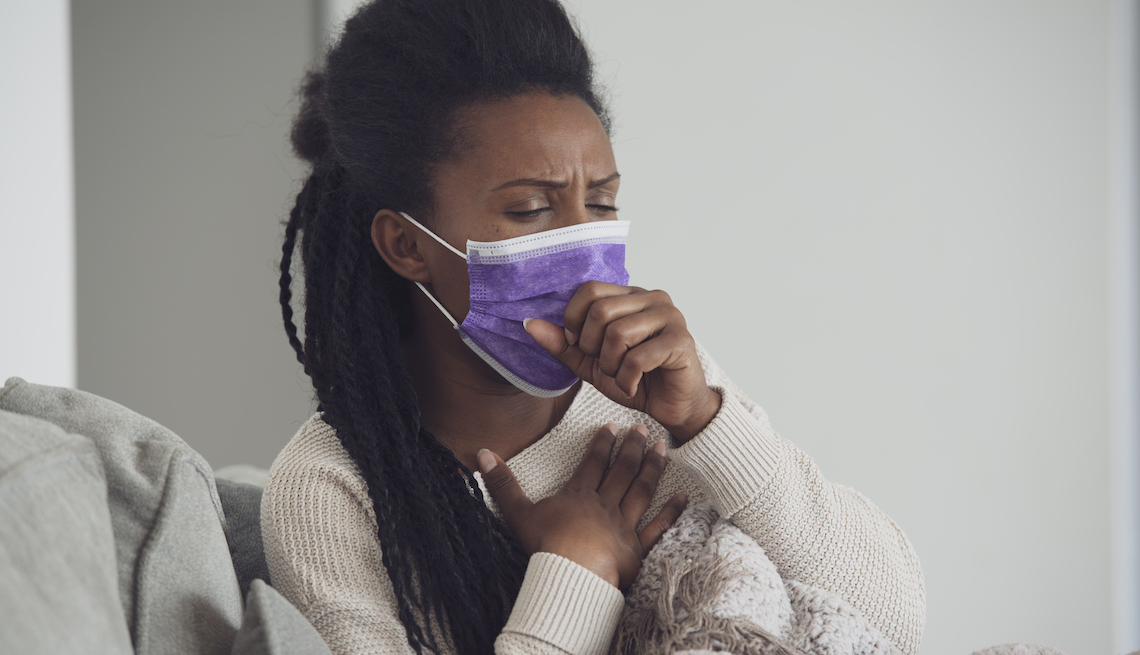 black woman in a purple face mask coughing