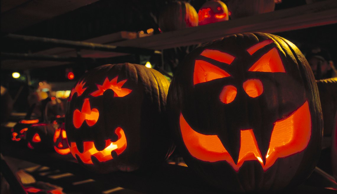 Scary carved jack-o'-lanterns, lit by candles, at a New Hampshire pumpkin festival