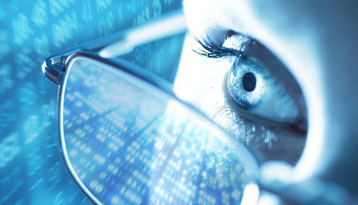 Acercamiento a un ojo de una mujer que usa lentes y una pantalla con datos en el fondo.