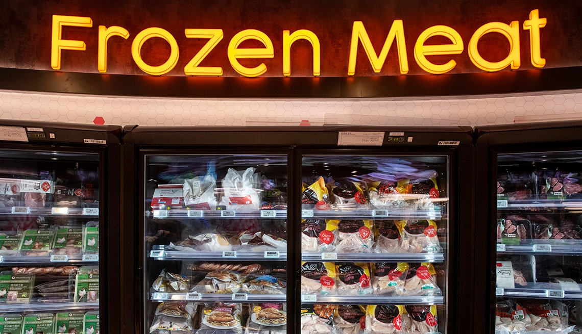 Display case of frozen meats with a sign saying frozen meat above the freezers.