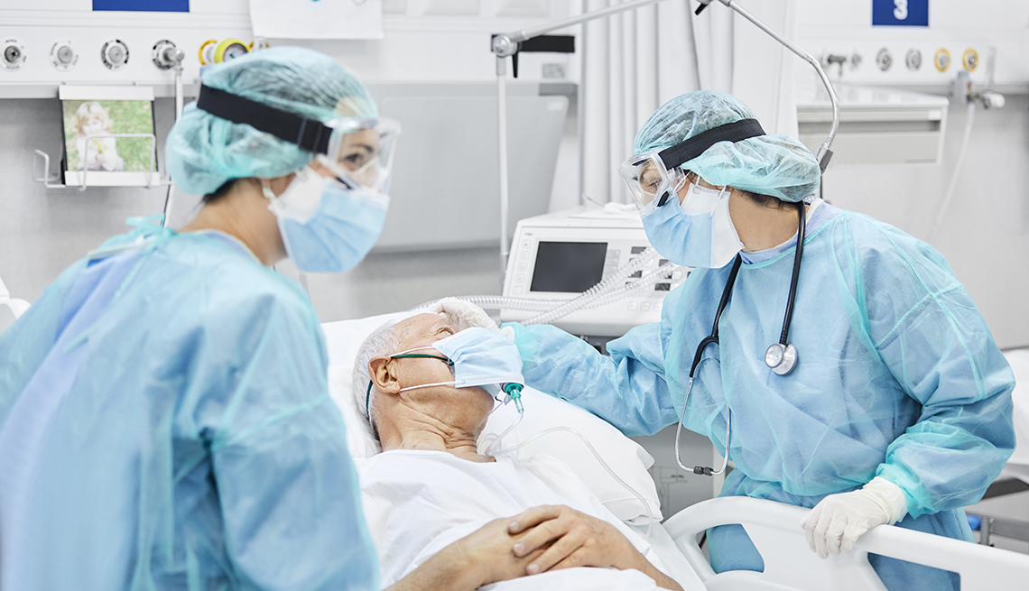 Doctors in protective equipment treat a patient in a hospital bed wearing a mask.