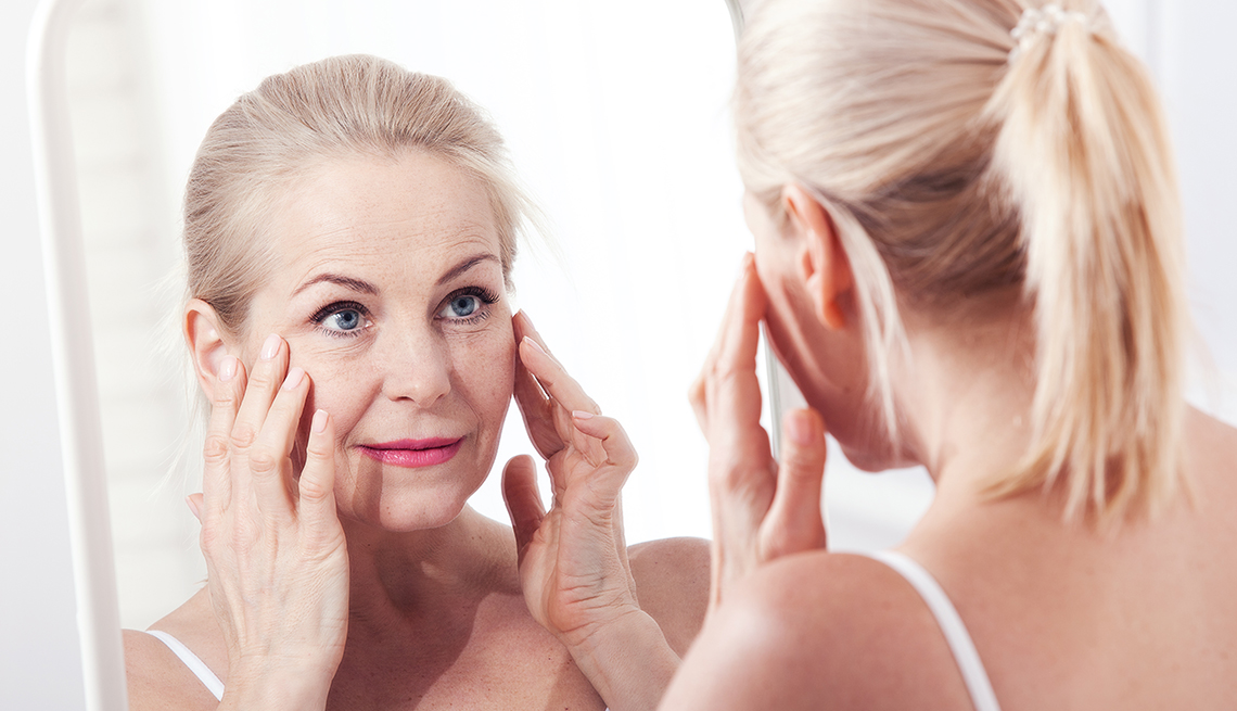 Woman inspects the skin around her eye in the mirror