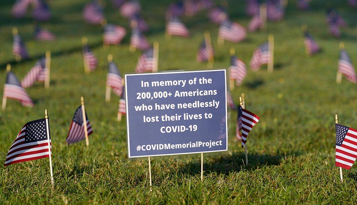 Banderas estadounidenses rodean un letrero azul que tiene la cantidad de personas que han muerto por COVID