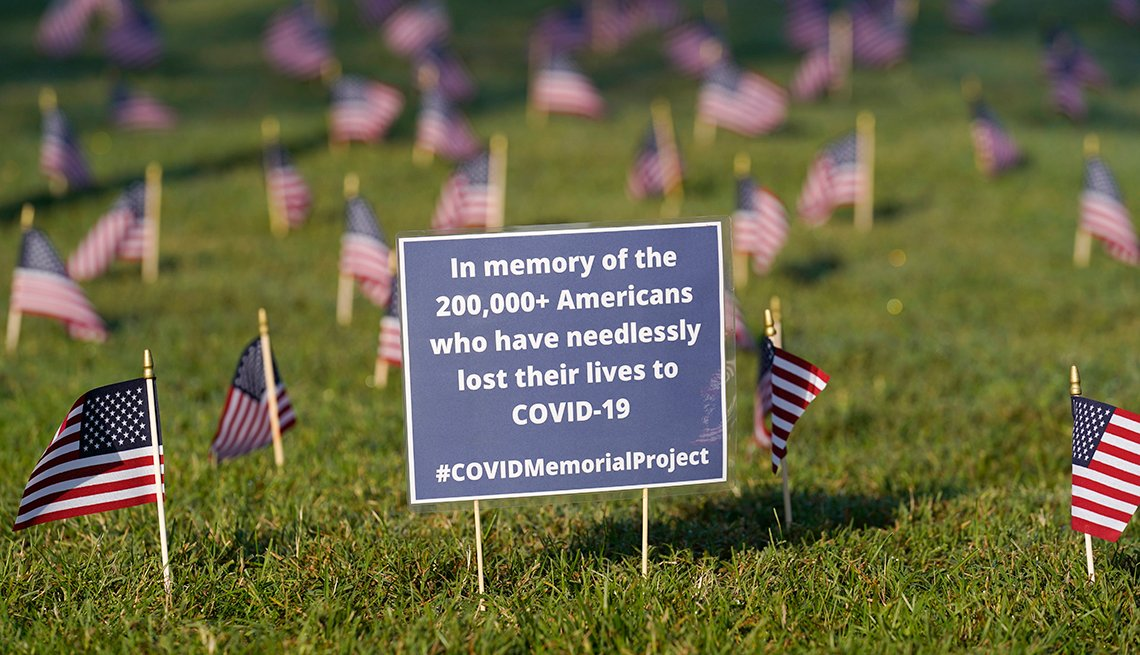 American flags surround a blue sign that has the amount of Americans that have died from covid nineteen