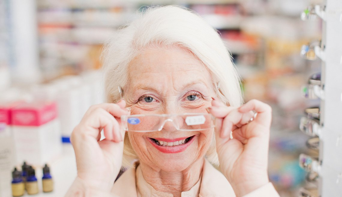Woman trying on reading glasses at the drugstore.