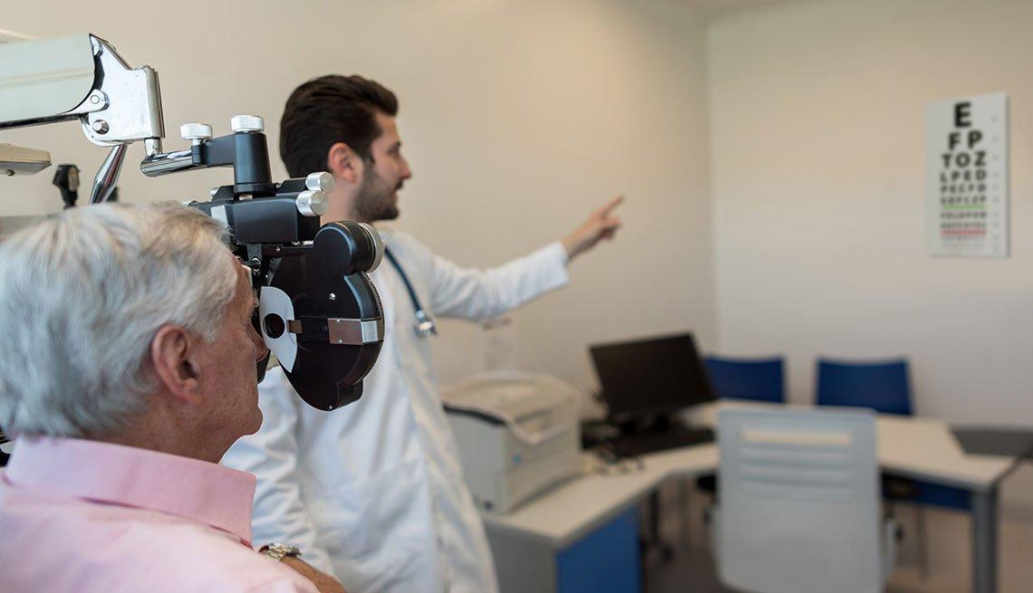 Médico le hace un examen de la vista a un paciente