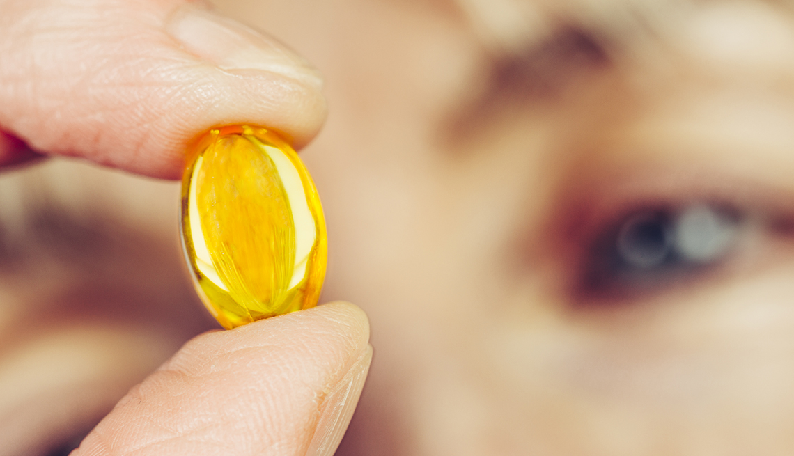 Closeup of a woman looking at a supplement pill.