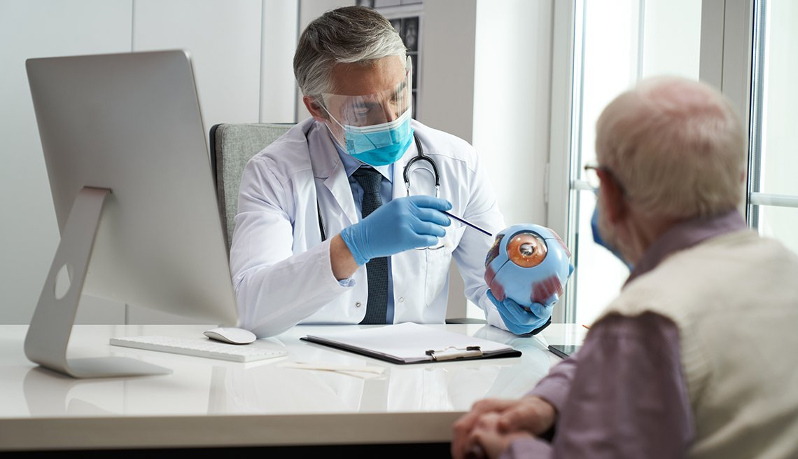 Doctor pointing to a model of an eye while a male patient watches. Both are wearing face masks.