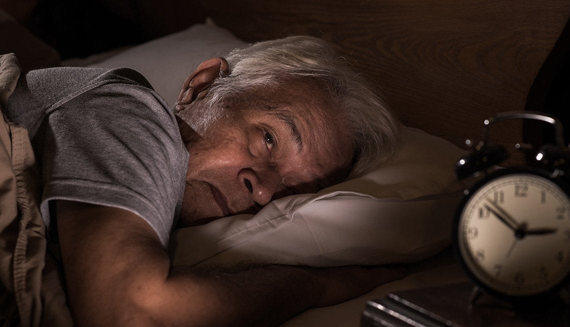 Un hombre mayor acostado en su cama y sin poder dormir