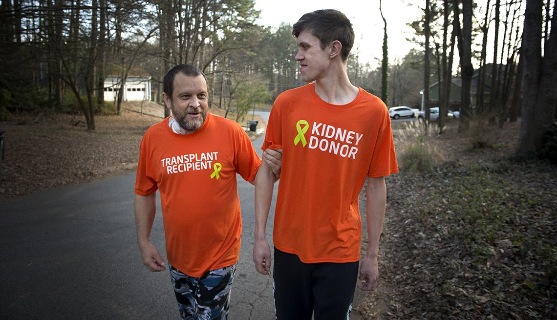Father and son walking arm in arm, father's t-shirt says transplant recipient, son's t-shirt says kidney donor.