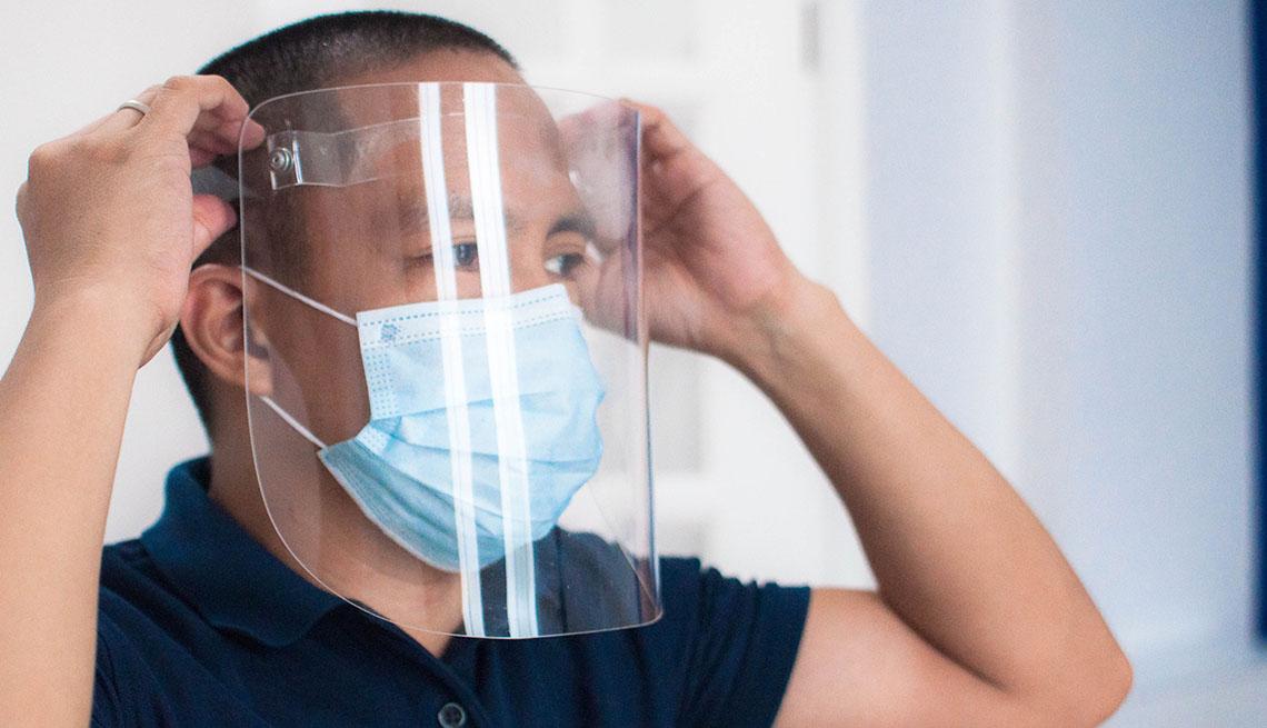 Un hombre se coloca un protector facial y también usa una mascarilla