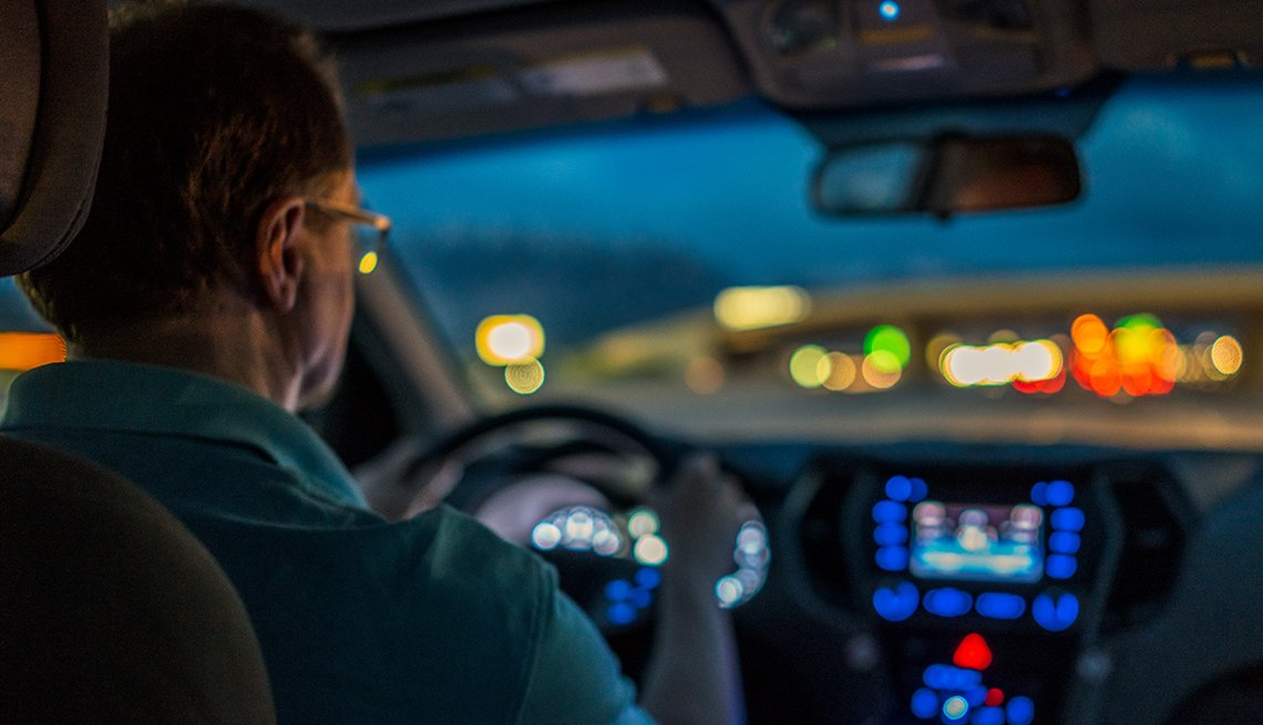 Man in his car, driving at night. Lights look blurry through the windshield.