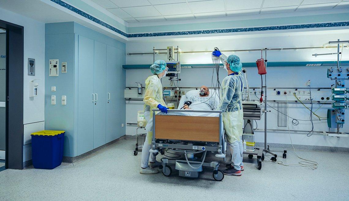 Personal médico atiende a un hombre en una cama de hospital