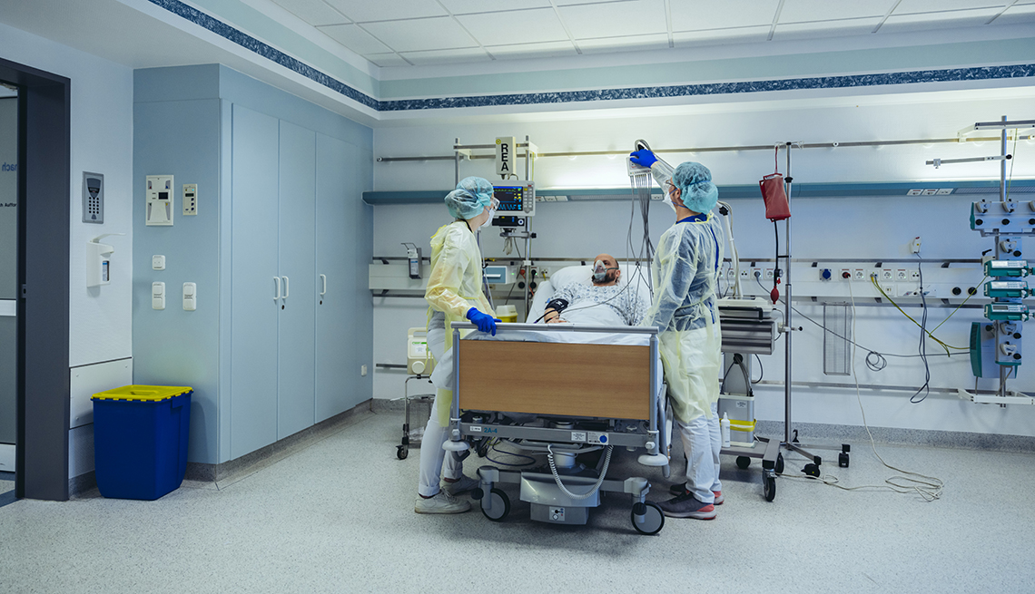 Medical staff caring for a man in a hospital bed.