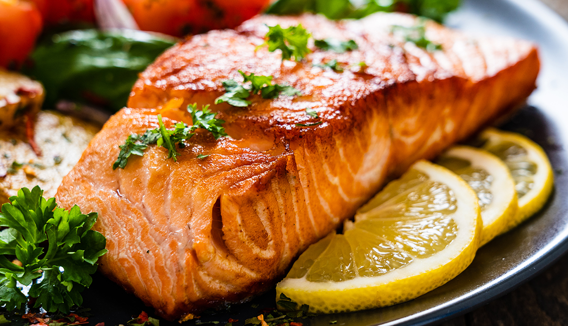 item 8 of Gallery image - Cooked salmon on a plate with lemon slices and vegetables