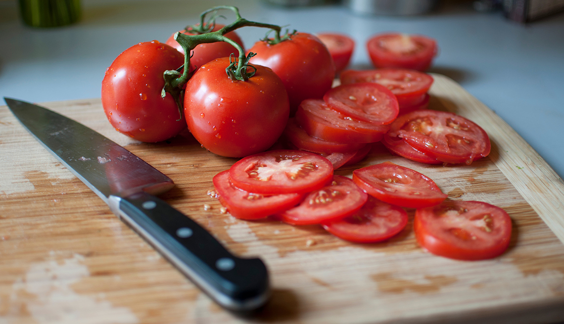 item 10 of Gallery image - Whole and sliced tomatoes on a cutting board with a knife.