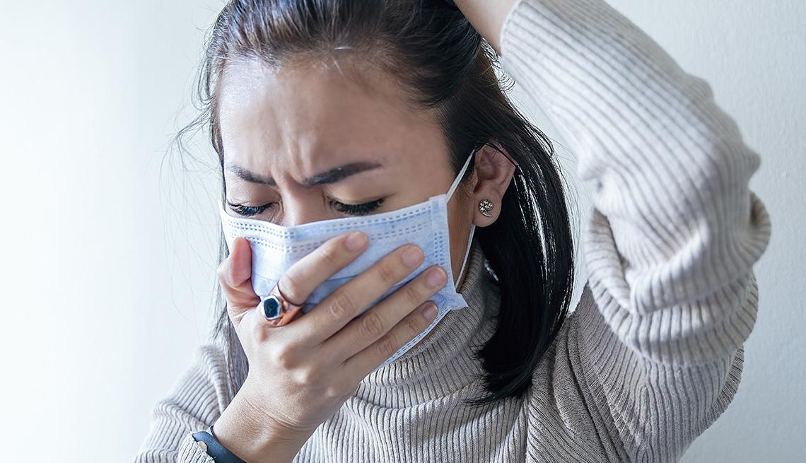 Una mujer usando mascarilla mientras estornuda y se aguanta la cabeza