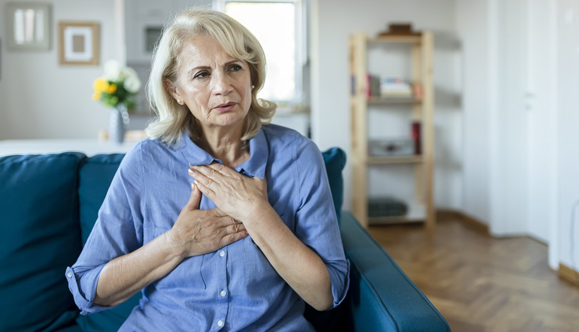 woman suffering chest pain while sitting on sofa at home
