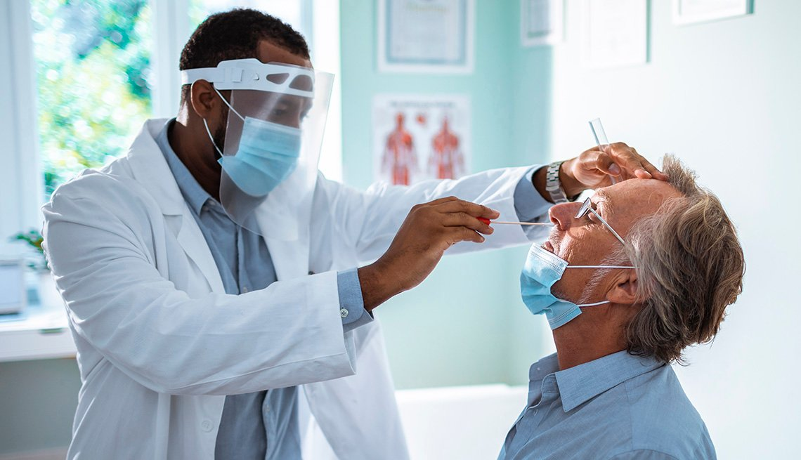 man having a nasal swab test done by a medical provider