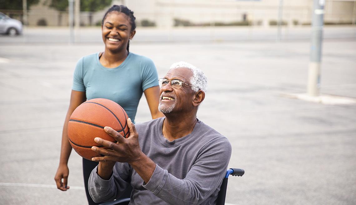 Hombre en silla de ruedas tira una bola de baloncesto mientras una mujer lo observa