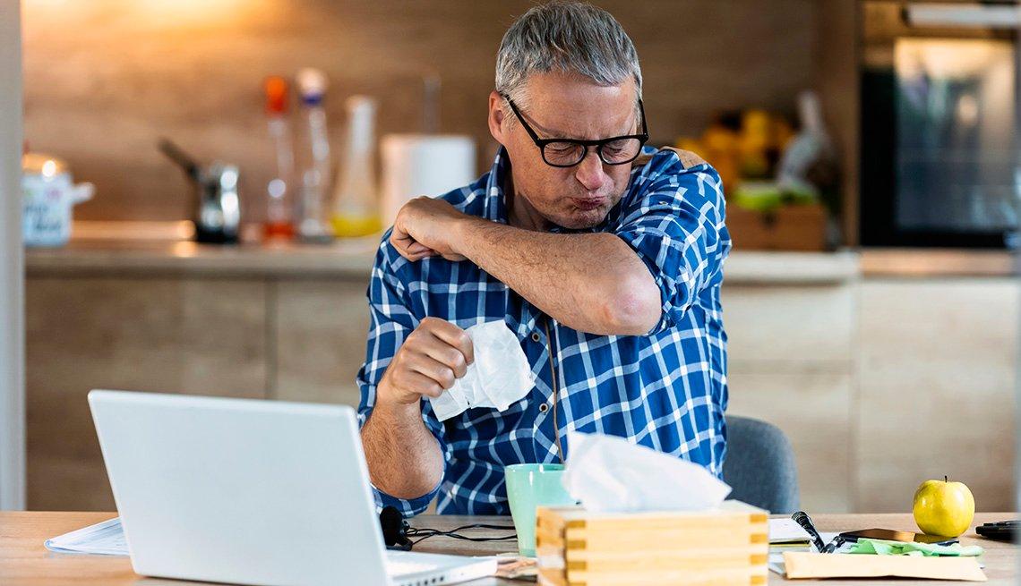 Un hombre estornuda en su codo