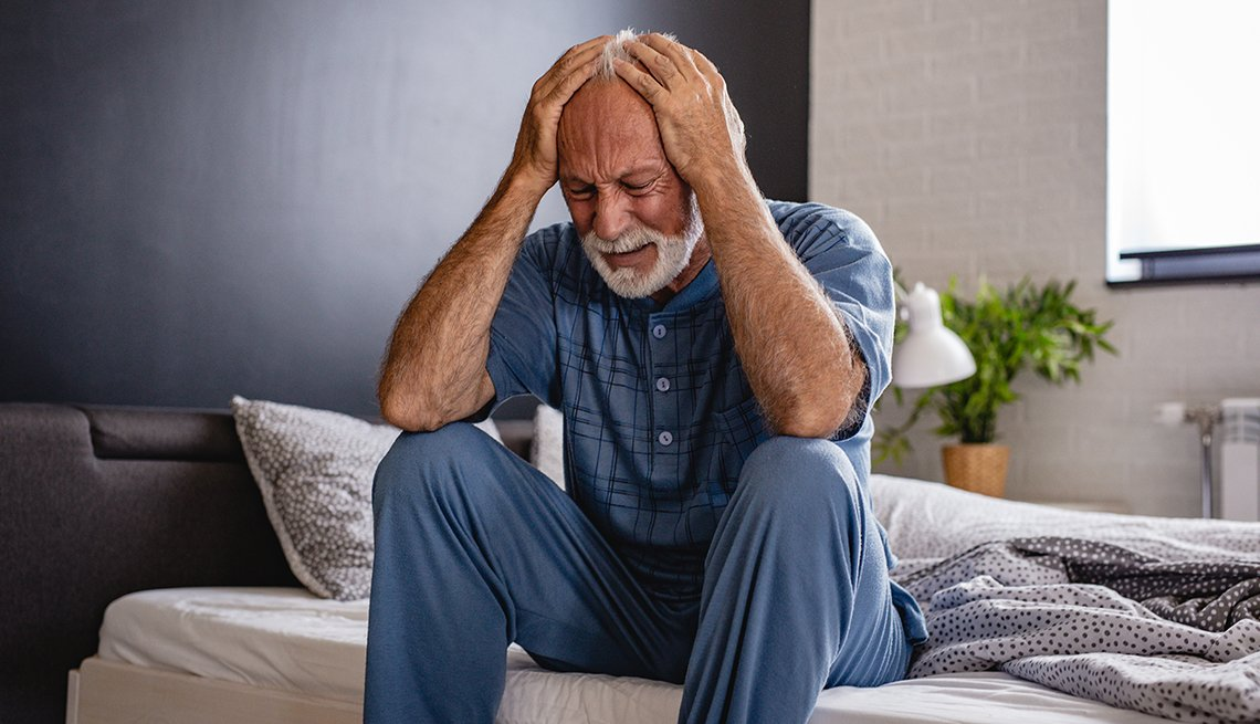 man sitting on the edge of his bed, holding his head in his hands, looks distressed
