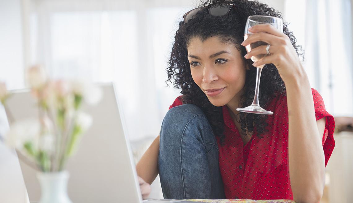 Una mujer toma una copa de vino mientras hace una búsqueda en su computadora