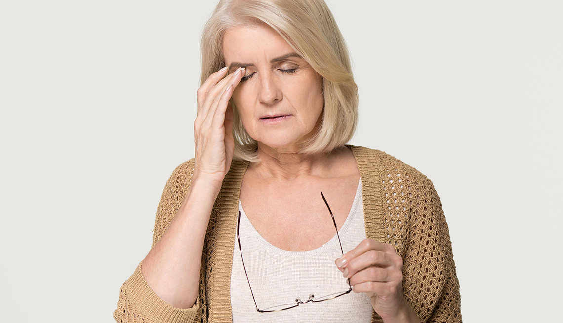 Woman touching her eyes, she looks uncomfortable.