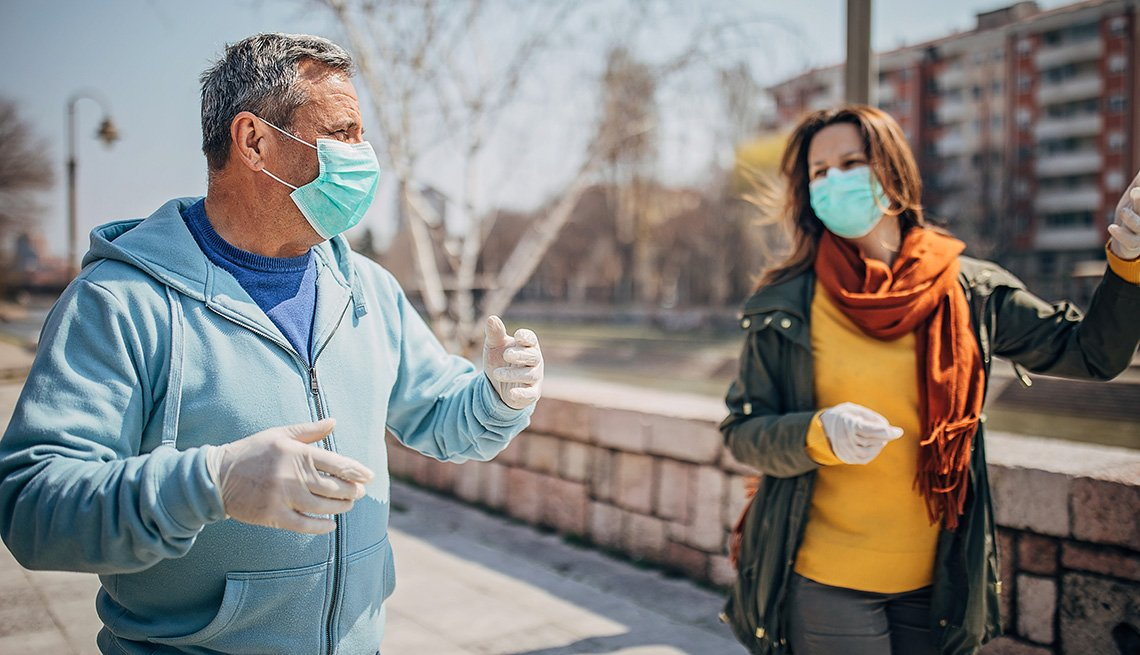 Man and woman walking outdoors wearing face masks.