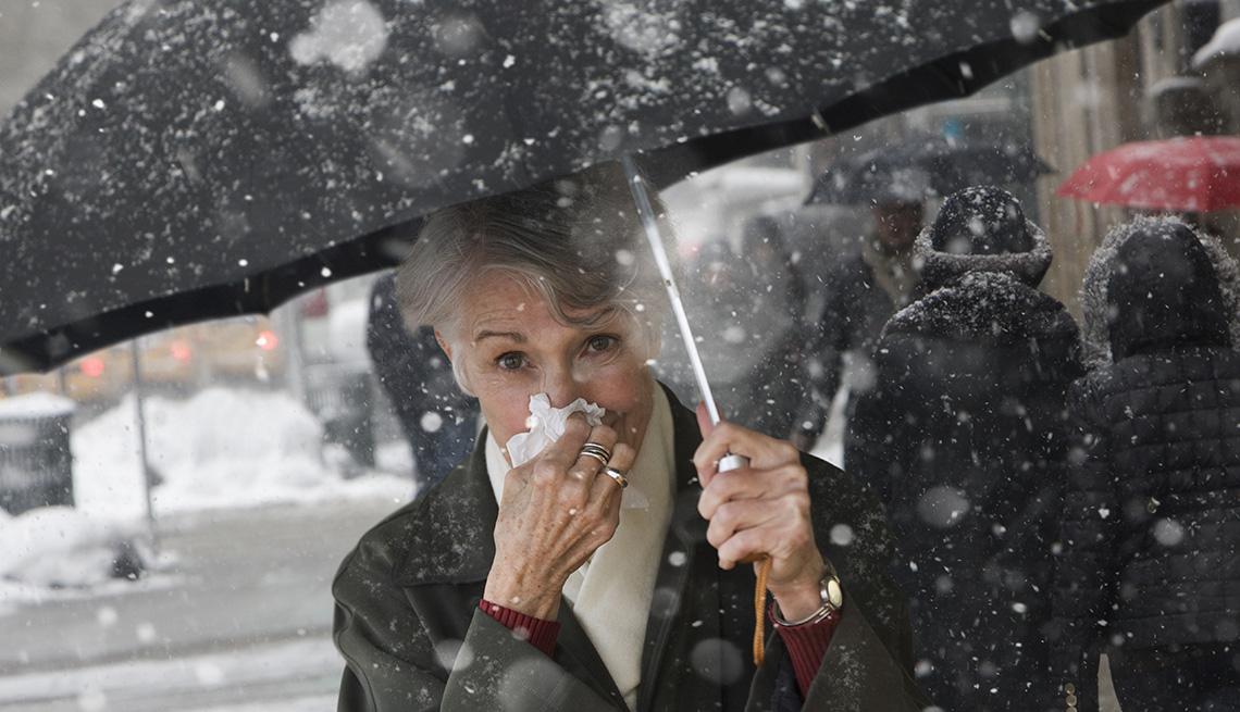 Una mujer limpia su nariz con un pañuelo mientras camina con una sombrilla bajo la nieve