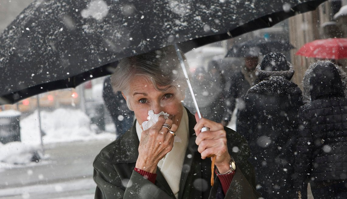 Woman outside in the snow holding an umbrella and blowing her nose.