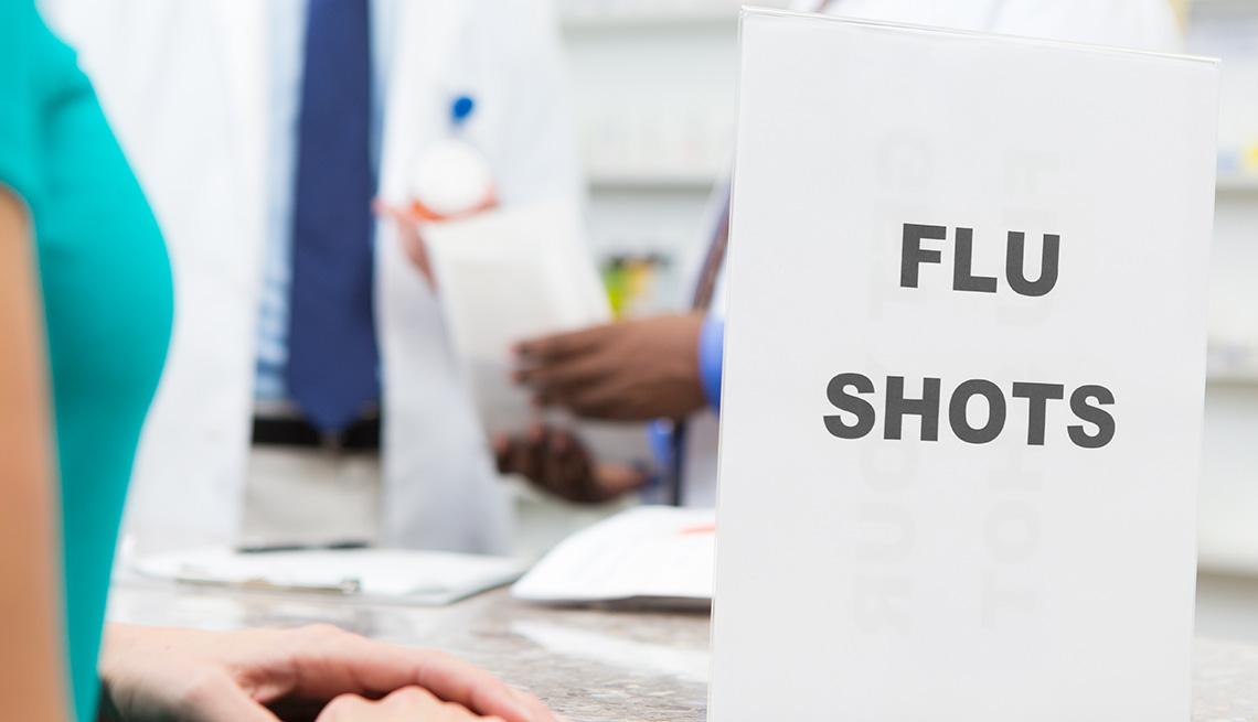 Mujer frente a un mostrador de una farmacia donde hay un letrero que dice vacuna contra la gripe