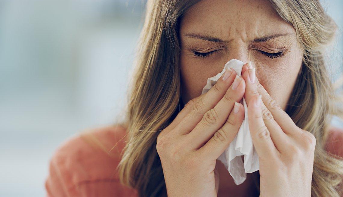 Una mujer estornuda en un pañuelo