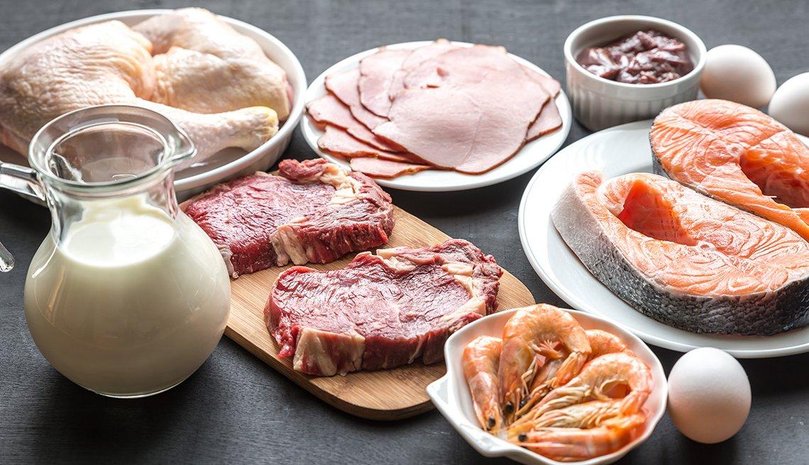 Platos de carne, pescado, pollo y huevos y una jarra de leche