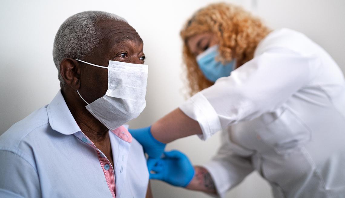 Enfermera vacuna en el brazo a hombre con mascarilla