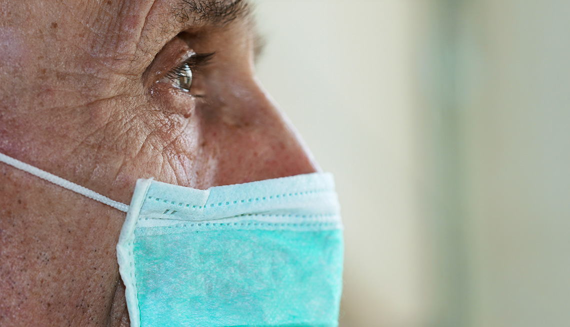 Man staring at the distance, looking concerned and wearing a face mask.