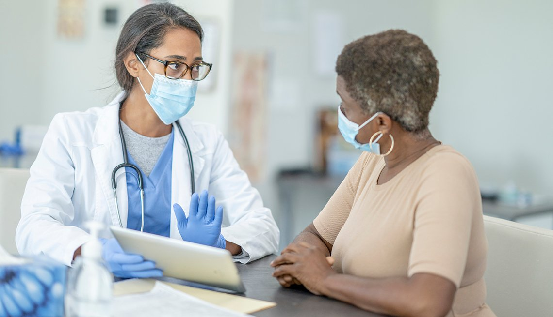 a woman talking to her female doctor about her mammogram results. both women are wearing face masks