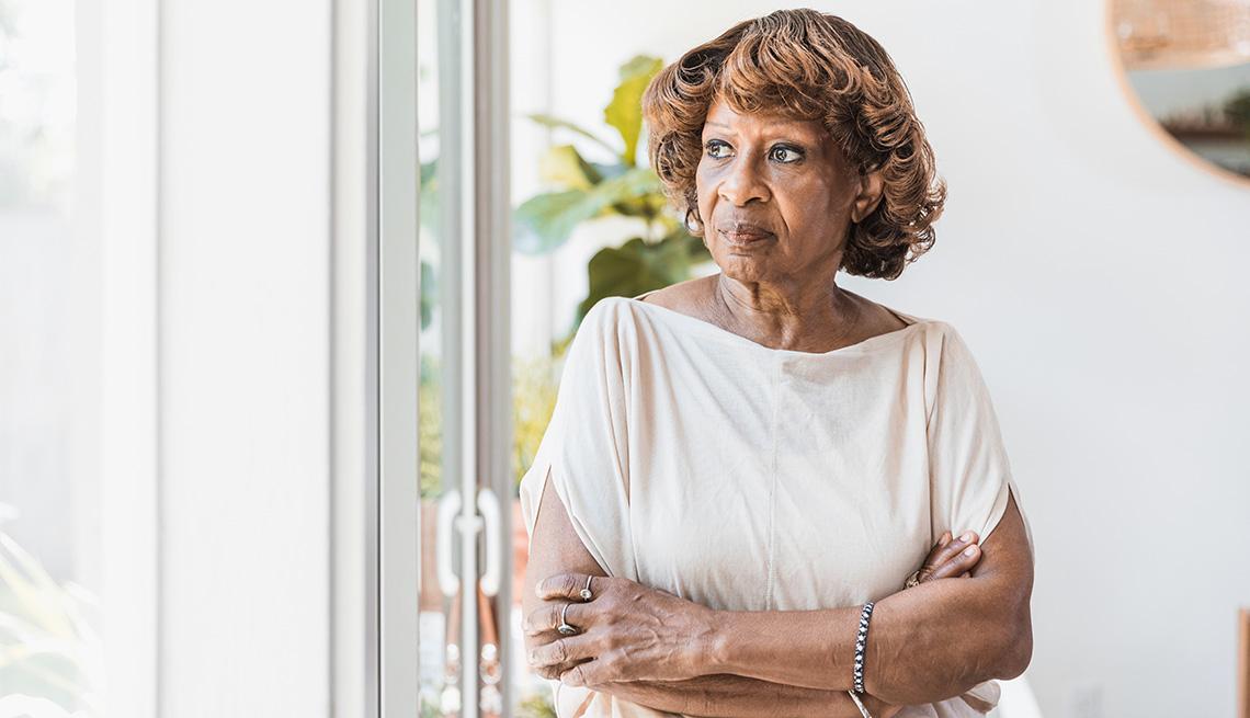 Una mujer afroamericana mira por una ventana