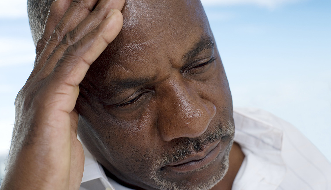man with his head in his hand, looking depressed