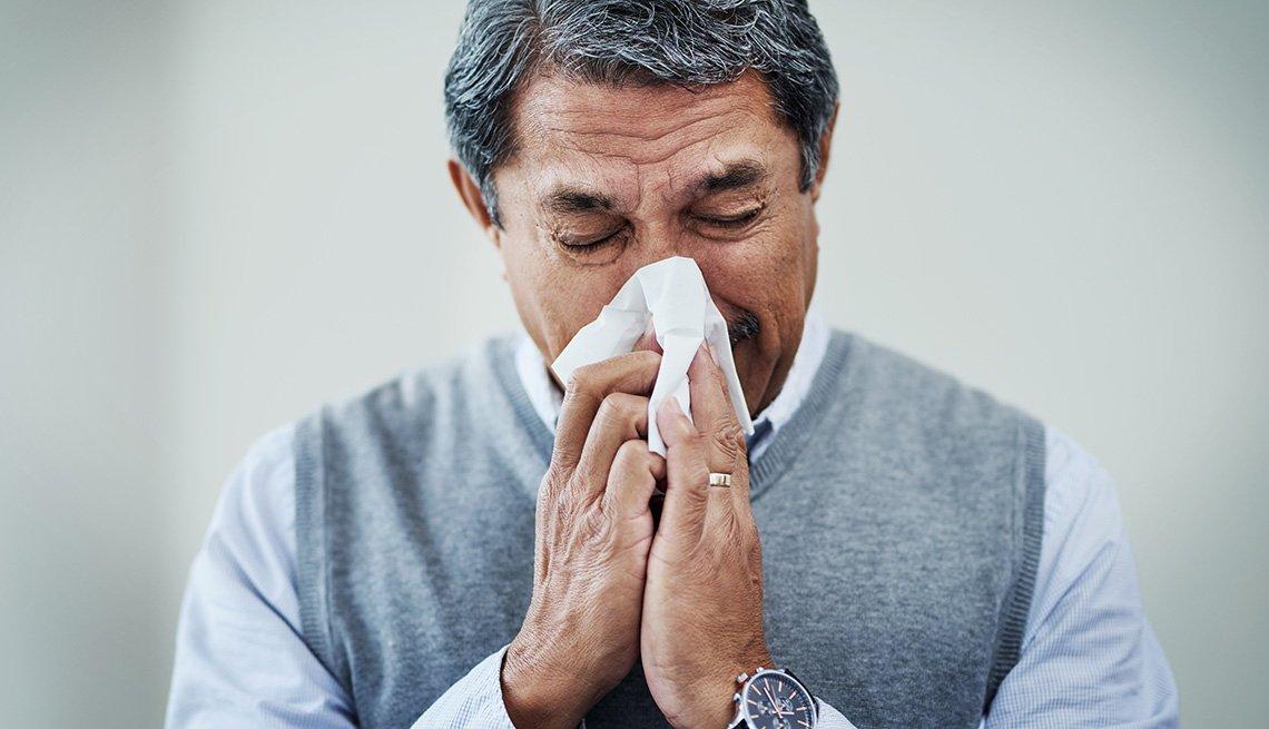 Un hombre sacude su nariz en un pañuelo