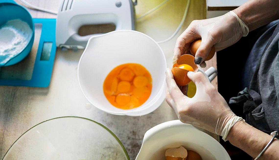 Un hombre abre varios huevos en un envase