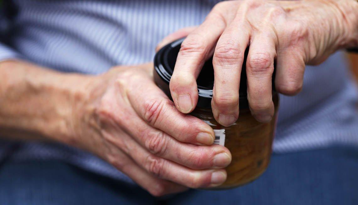 Una mujer mayor intentando abrir un frasco