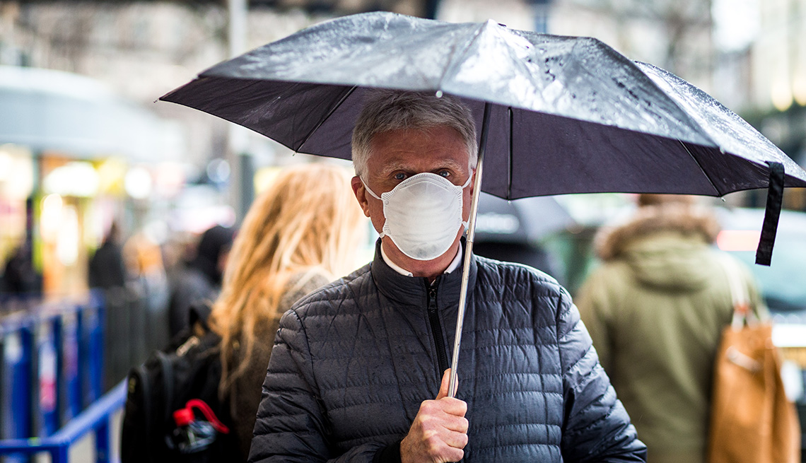 Man walking outside in rainy fall weather. He is wearing a face mask and carrying an umbrella